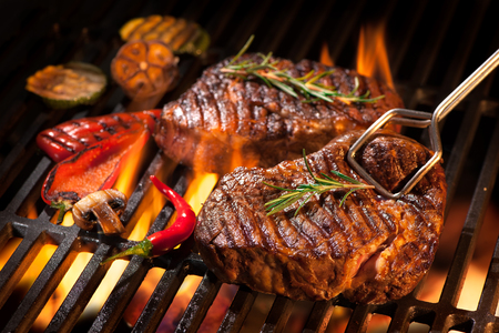 52913995 - beef steaks on the grill with flames