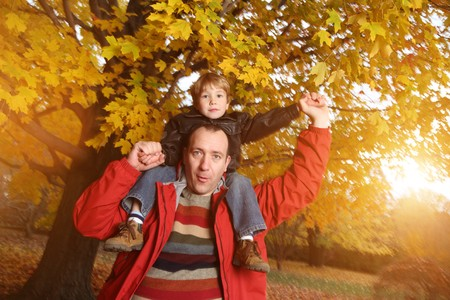 7784925 - portrait of happy father giving son piggyback ride on his shoulders in autumn park.