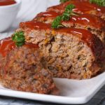 33987918 - sliced meatloaf with ketchup and parsley closeup on a white plate, horizontal