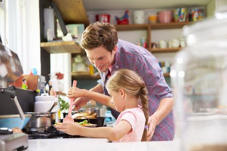 41461570 - daughter helping father to cook meal in kitchen