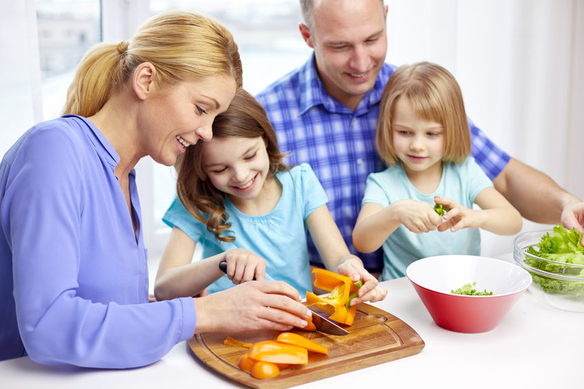 47304482 - food, children, culinary and people concept - happy family with two kids cooking vegetables at home
